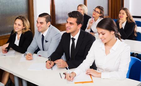Photo pour Professor and positive young professionals at extension business courses - image libre de droit