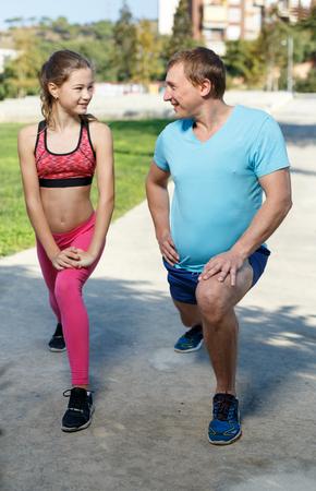 Foto de Smiling sporty man and tweenager girl doing exercises together in summer park - Imagen libre de derechos