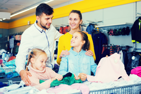 Young smiling family of four looking for children clothes on shelves in store. Focus on woman
