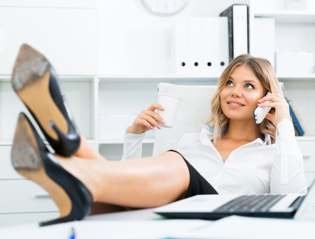 Photo for Relaxed girl threw her legs on table and spoke on phone at office - Royalty Free Image