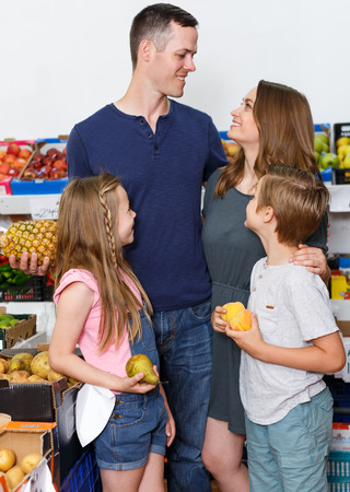 parents with children standing near shelves with fruits  in local supermarket