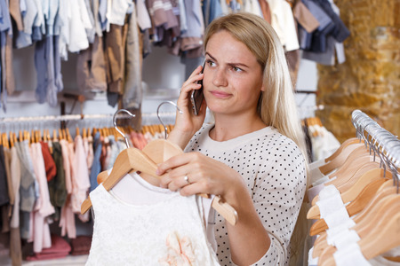 Cheerful girl standing in kids clothes boutique and choosing white holiday dress for her little daughter using phone