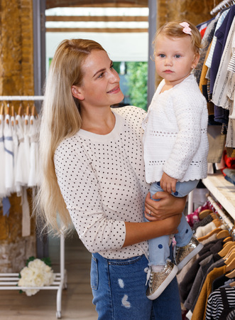 Young mother and her little daughter choosing baby clothes in shop