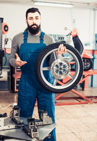 Work motorcycle repair shows the repaired tire on a scooter
