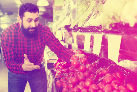 Photo for Glad male seller offering tomatoes in grocery shop - Royalty Free Image