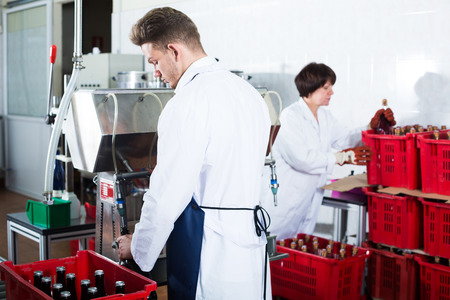 Adult man worker bottling sparkling wine with machine at wine factory