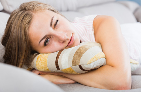 Young woman lying with one closed eye on sofa in living room