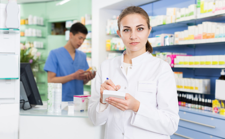 Young female pharmacist is attentively checking medicine to notebook in apothecary