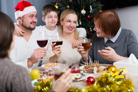 Photo pour Cheerful family at dining table for Christmas dinner against backdrop of decorated fir tree - image libre de droit