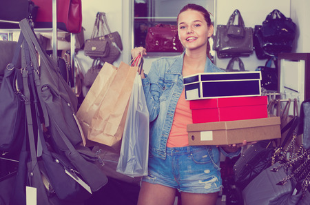 Smiling cheerful glad teenager girl shopping in store with bags and accessories