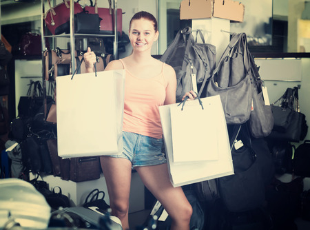 happy teenager girl holding shopping bags in fashion boutique