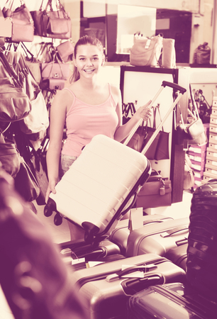 Glad  positive teenager girl buying large wheeled plastic luggage bag in shop