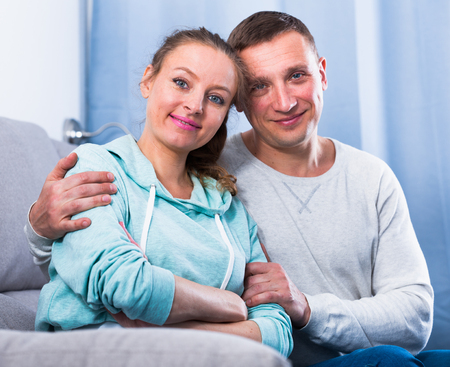 Middle-aged husband and wife enjoying quiet evening together at home