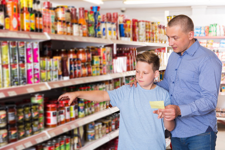 positive adult father doing shopping with  boy looking at shopping list while choosing fresh products in food store