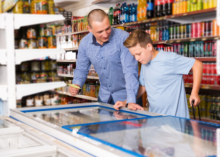 happy young father doing shopping with preteen boy looking at shopping list while choosing fresh products in food store