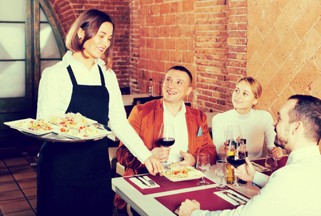Beautiful female waiter carrying order for visitors in country restaurant