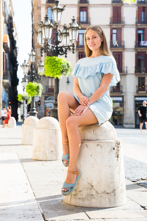 Attractive smiling girl in lightweight blue dress sitting on stone bollard in historical center of Barcelona