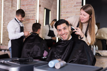 Female hairdresser cutting hair of male client with electric clipper in hair salon