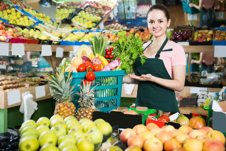 Smiling british salesgirl in store with basket filled with fresh fruits and vegetables