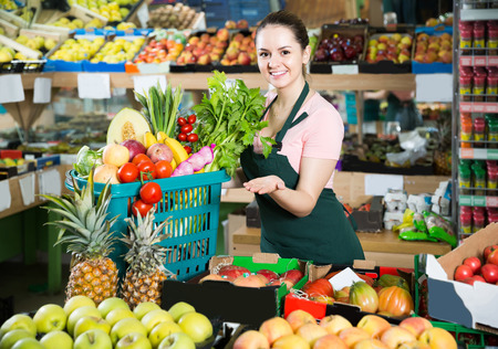 Smiling italian salesgirl in store with basket filled with fresh fruits and vegetables