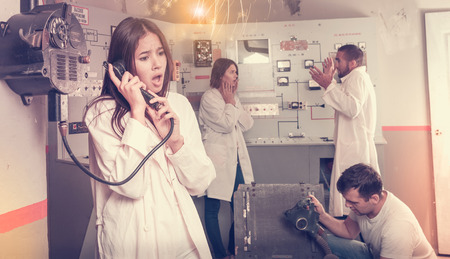 Photo pour Emotional girl using telephone set while trying to get out with friends of escape room stylized as underground shelter - image libre de droit