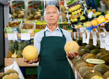 Positive glad  smiling senior male owner of greengrocery shop in apron offering fresh fruits and vegetables for sale