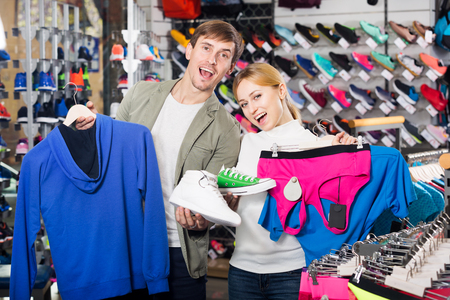 Young man and woman choosing and fitting clothing in the sport department. Focus on man