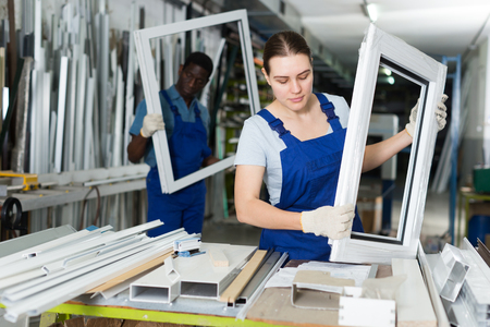 Portrait of woman worker who is standing with window frame in the pvc workshop.