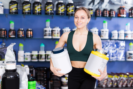 Cheerful athletic female holding plastic jar of sports nutritional supplements in shop interior