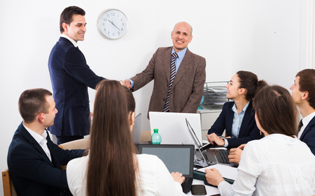 Firm handshake between two business partners at the office meeting