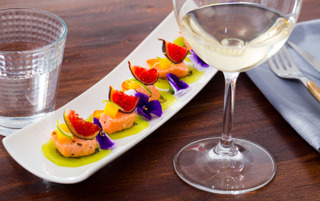 Exotic ceviche of pickled salmon served on circles of fresh kiwi with figs, cumquat, lime zest and blue pansies