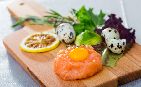 Tartare of fresh salmon on wooden board. Recipe: finely chop 200 gr of fish, season with salt, black pepper, olive oil, lemon juice, garnish with yolk of quail egg, greens and balsamic vinegar