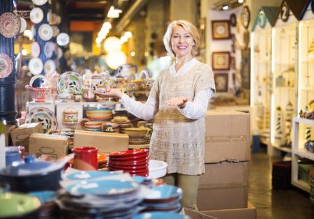 Photo pour Mature glad blonde woman chooses ceramic ware in the cookware section at hypermarket - image libre de droit