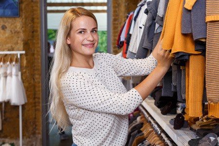 Positive young woman shopping in kids clothing store