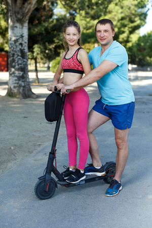 Foto de Happy friendly family of father and preteen girl wearing sports clothes riding scooter outdoors - Imagen libre de derechos