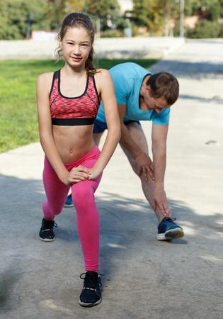 Foto de Slim preteen girl and her athletic father spending time together during workout outdoors - Imagen libre de derechos