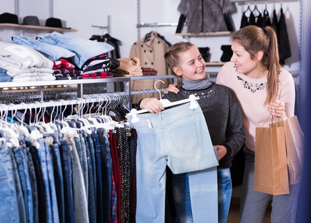 Cheerful daughter with young mother choosing new stylish jeans in retail store