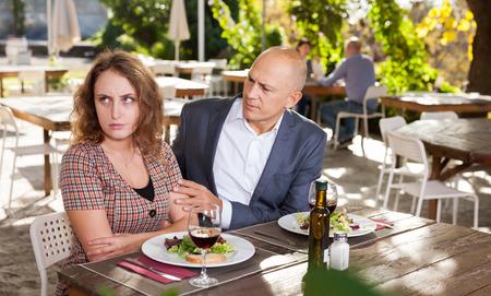 Photo pour Family quarrel during lunch in an open-air restaurant - image libre de droit