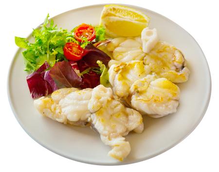 Foto de Healthy dinner, baked white fish steak with lemon and greens. Isolated over white background - Imagen libre de derechos