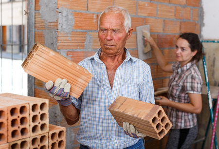 Photo pour Skillful older man with young woman installing brick wall in building under construction - image libre de droit