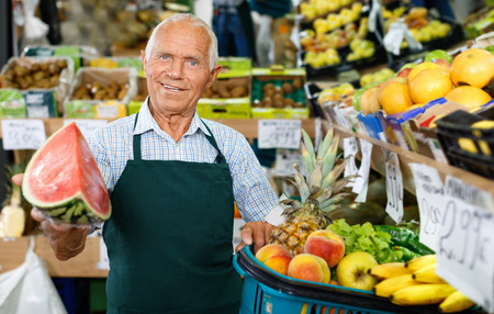 Cheerful glad  smiling senior male owner of greengrocery shop in apron offering fresh fruits and vegetables for sale