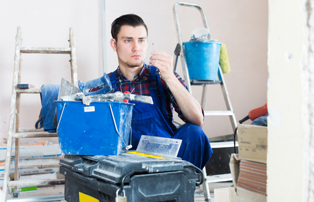 Positive adult worker repairing room and looking for necessary tool in toolbox