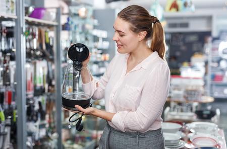 Photo pour Young woman  housewife looking electric kettle in kitchen appliances section - image libre de droit