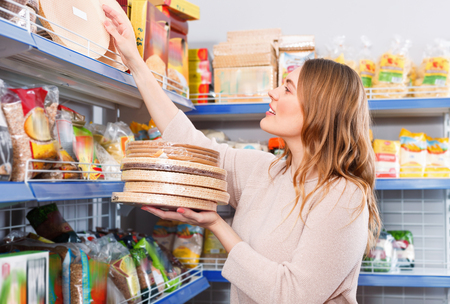 Photo pour Adult smiling  woman customer choosing biscuit layers in  grocery food store - image libre de droit