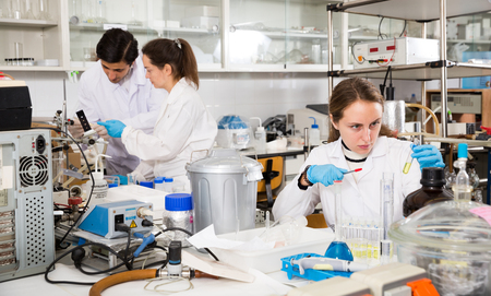 Portrait of young woman lab technician writing report on results of chemical experiments in notebook