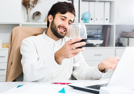 Foto de Cheerful brunette man holding glass of red wine and having video chat at office - Imagen libre de derechos