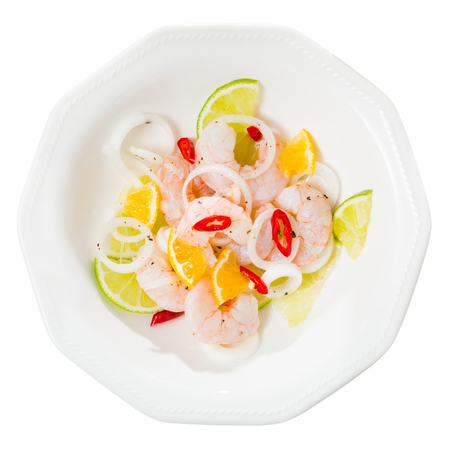 Delicious shrimp ceviche with lime, tangerine, onion and hot pepper served on white plate. Isolated over white background