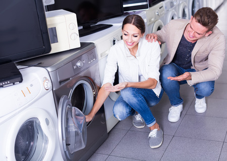 Photo pour Young happy couple choosing washing machine in hypermarket and smiling - image libre de droit