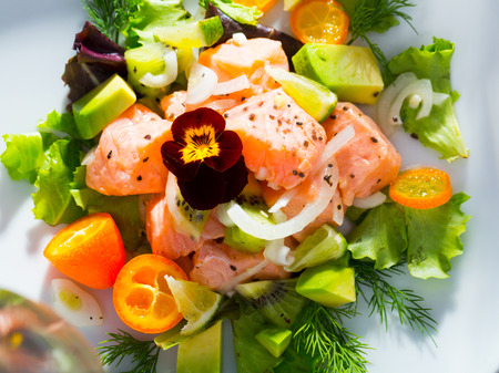 Tasty fish ceviche with chopped ripe avocado, juicy kumquat, lettuce leaves and dill on white plate