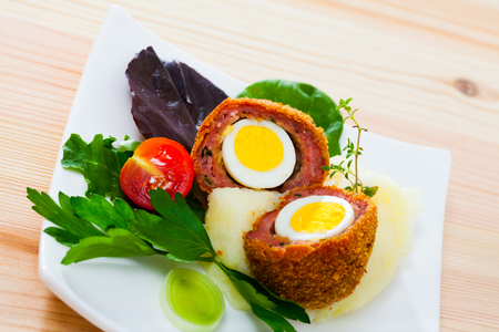 Hard-boiled quail egg wrapped in sausage meat, breaded and fried (Scotch egg) served with pureed potatoes, baked carrots, cherry tomatoes and greens